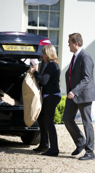 Police were pictured leaving Tulisa's home in Hertfordshire with two large bags