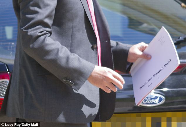 A police officer enters Tulisa Contostavlos's home today holding a search book