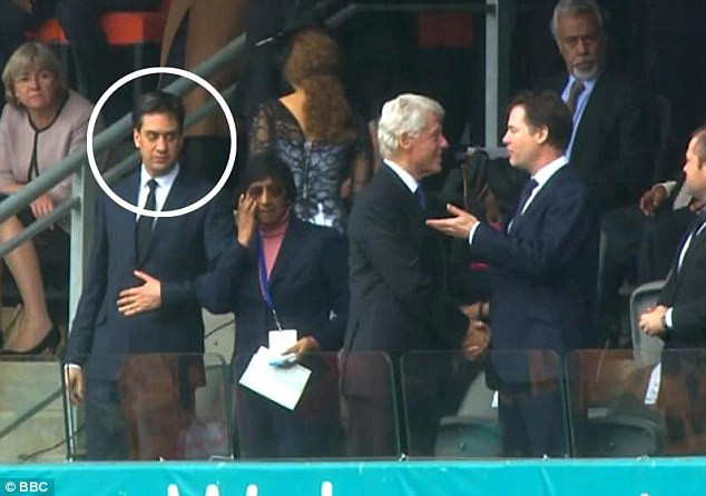 If looks could kill: Labour leader Ed Miliband appears to cast a cold stare towards Bill Clinton and Nick Clegg as they engage in animated discussions during Nelson Mandela's memorial