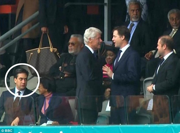 On the periphery: Mr Miliband continues to look agitated after he takes his seat... as the former U.S. President and deputy British Prime Minister carry on shaking hands