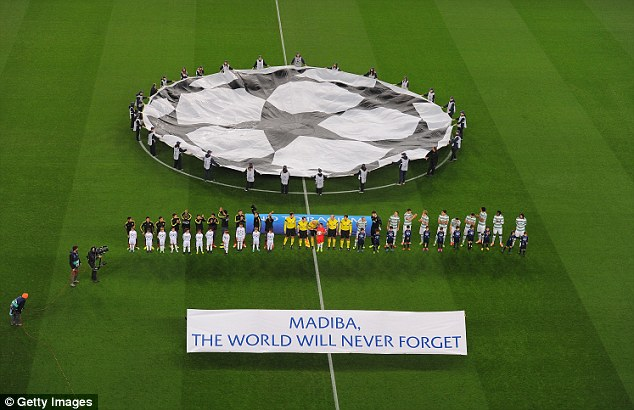 Tribute: Barcelona and Celtic players stand behind a banner in honour of Nelson Mandela