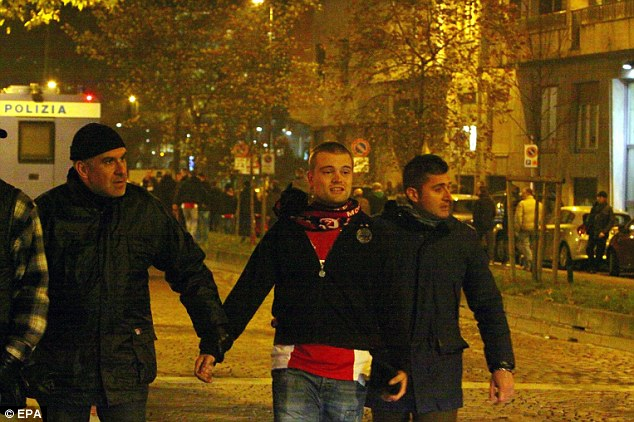 Caught: An Ajax fan is escorted away by two Italian Police officers