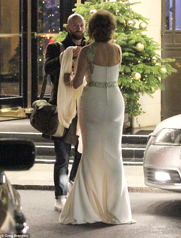 Here you go: Carol Vorderman is handed her flowing ivory robe by a gallant stranger as she leaves her London hotel on Wednesday evening