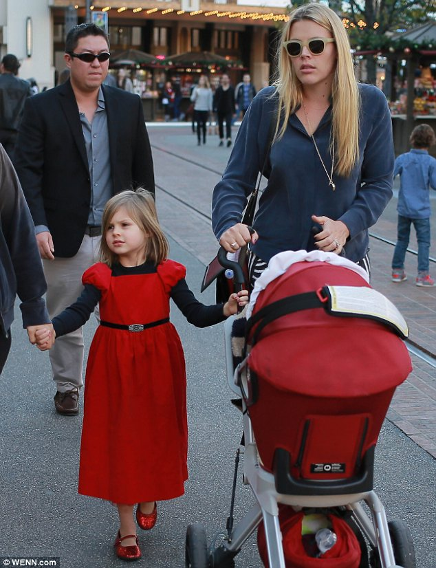 Festive family: Five-year-old Birdie was clad in a pretty red dress and ruby slippers, and even the stroller was red