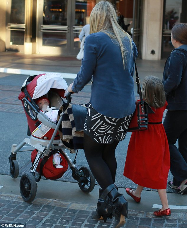 Teamwork: Busy pushed Circket's stroller through the shopping centre, while Birdie held a nanny's hand