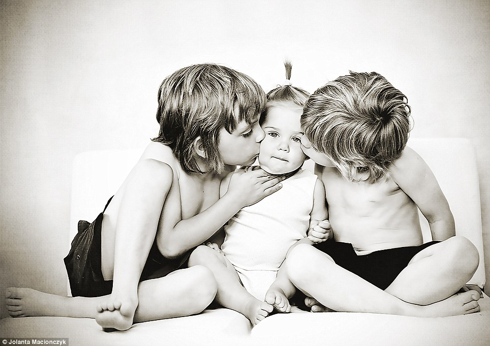 Brotherly love: This picture was taken by Jolanta Macionczyk for her grandparents. She said: 'They live far away and don't see their grandchildren very often. The brothers Olaf and Oscar really love their little sister Olivia and they wanted to show it by giving her a kiss'