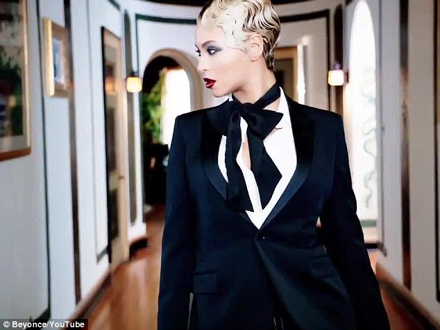 Forceful: Beyonce struts down a corridor wearing a man's tuxedo suit with a tie around her neck