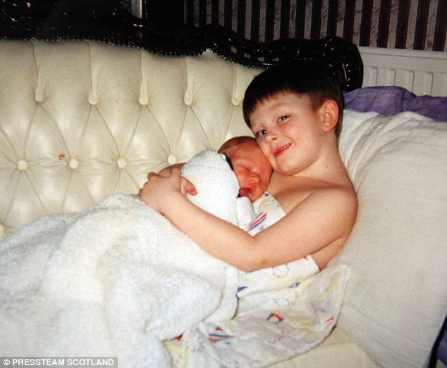 What a sweetie! The star holds his newborn sister in his arms