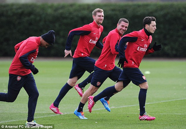 German class: Gunners trio Per Mertesacker (second left) Lukas Podolski (second right) and Mesut Ozil (right) are aiming to fire Arsenal to Premier League glory this season... and it hasn't started too badly!