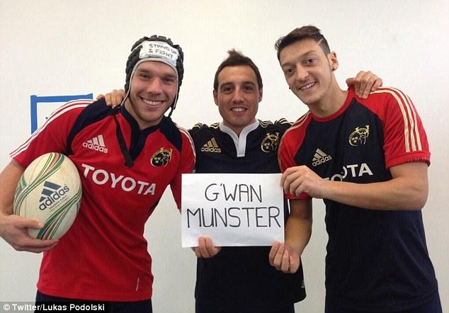 Support: Podolski (left), Santi Cazorla (centre) and Mesut Ozil (right) show their Rugby allegiance...