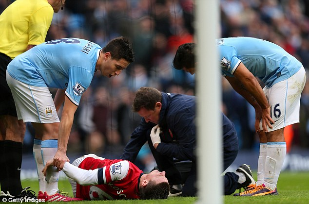 In pain: Arsenal lost Laurent Koscielny to a knee injury in the first half