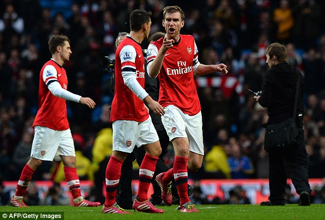 German bust up: Per Mertesacker has a world with Mesut Ozil as they make their way off the pitch