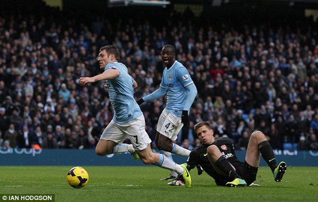 To the ground: Szczesny brought down James Milner in injury time to concede a penalty