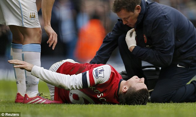 Concern: Koscielny writhes in pain after the challenge