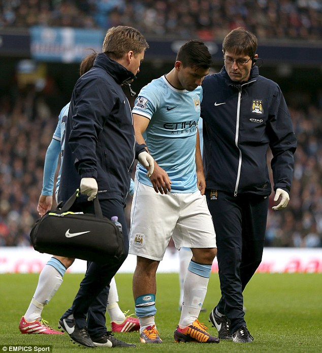 Ouch: Manchester City striker Sergio Aguero is helped off the pitch by the club's medical staff against Arsenal