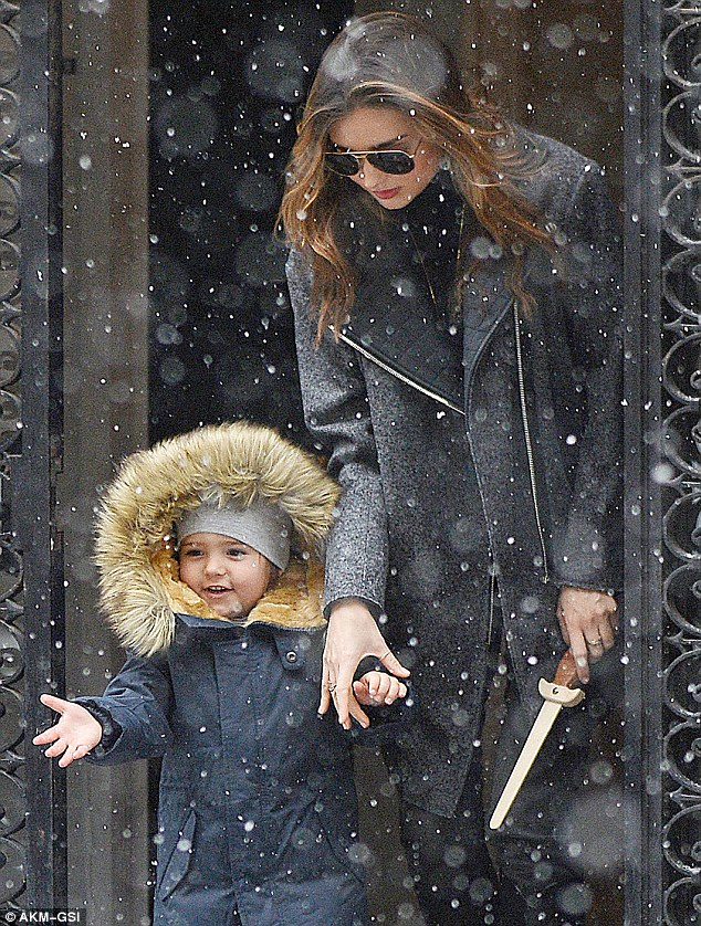Excited: Flynn put out his hand to catch a flake as his mother kept a tight hold of him