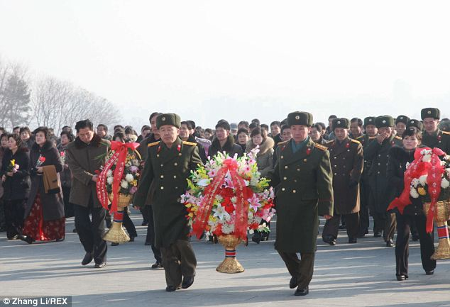 Another photo showed a march by soldiers carrying red flags, watched by military leaders. It was not clear whether Jong-Un was among them.