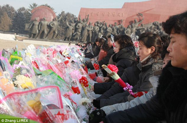 Pertinent: Citizens lay flowers at the site under the shadow of a nationalistic sculpture of workers cheering their leaders