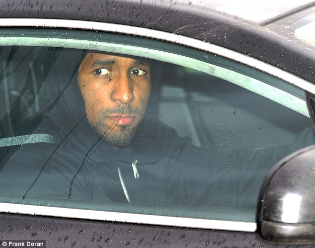 Moving on: Jermain Defoe drives past the waiting photographers after the news of his manager's sacking