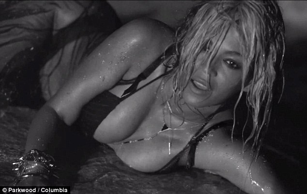 Embracing her wild side: Beyoncé rolls around on the sand in the nighttime black and white beach shoot for the newly-released sexually explicit track Drunk In Love