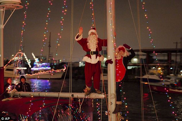 Yo ho ho! Santa waves from the mast of a decorated sailboat as blaze a bright trail out to Galveston Bay during the Saturday parade