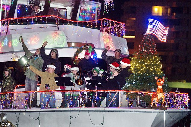 The most famous reindeer of all: Participants in the 27th Annual Holiday on the Harbor Lighted Boat Parade in Destin, Florida wave to onlookers on Sunday