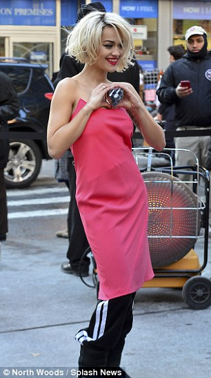 Pretty in Pink: The singer later changed into a pink dress and held a perfume bottle while making a heart shape with her hands