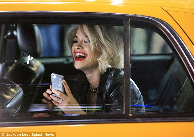 Tickled pink: The pop superstar was giggling away as she checked her phone in the back of a cab