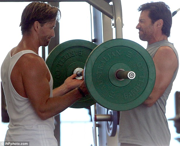 Getting pumped: A companion kept a close eye as Hugh Jackman curled a weight in Sydney, Australia on Wednesday