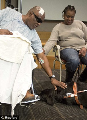 Blind man Cecil Williams pets his service dog Orlando following a press conference in New York December 18, 2013. Williams fell on the subway tracks with Orlando even as the dog tried to pull him away. REUTERS/Carlo Allegri (UNITED STATES - Tags: SOCIETY ANIMALS)
