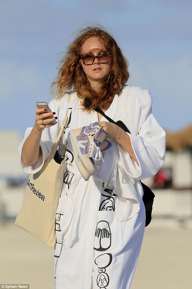 Lily Cole texts on her iPhone and carries her sneakers while walking on the beach in Miami Beach, Florida