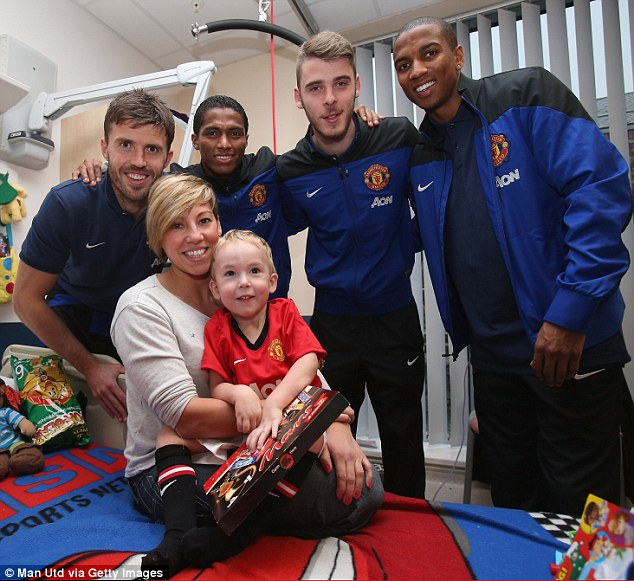 Day to remember: Carrick, Valencia, De Gea and Ashley Young (right) pose with a fan and his mother