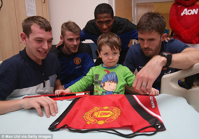 Visit: David de Gea (second left), Luis Antonio Valencia (back) and Michael Carrick (right) with one young fan