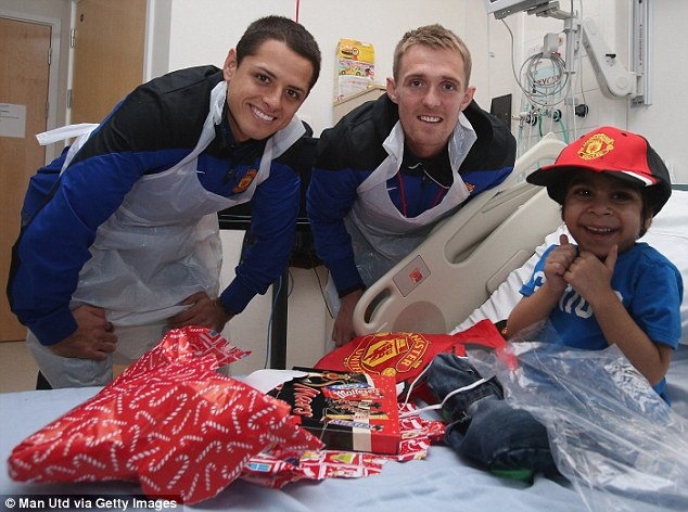 All smiles: One young United fan shows his delight at meeting Javier Hernandez and Darren Fletcher
