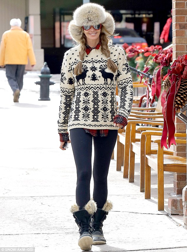 Hat trick: A smiling Elle looked something like Heidi Of The Mountains in her huge furry trapper's hat, blonde plaits, and wacky Christmas jumper on Thursday