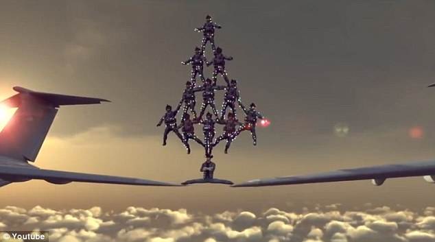 Legs of steel: Norris is shown in a spoof online video straddling the wings of two passenger planes with a human Christmas tree of skydivers balanced on his head