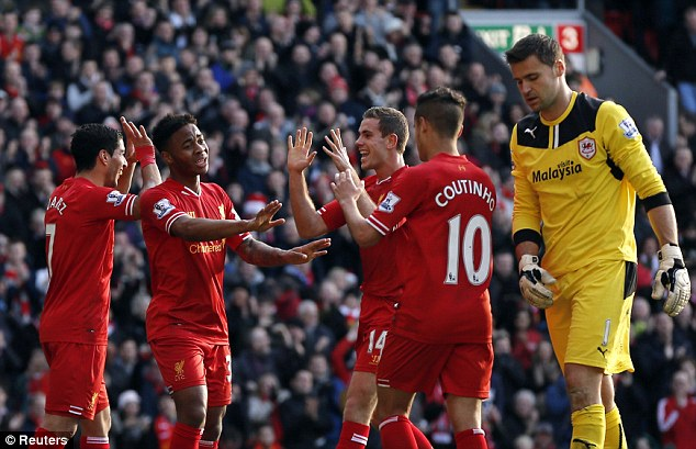 High fives: Sterling celebrates with his Liverpool team-mates after doubling their lead against Cardiff