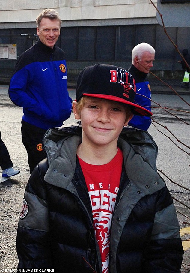 Timing: Manchester United manager David Moyes smiles for the camera as he walks past a young boy