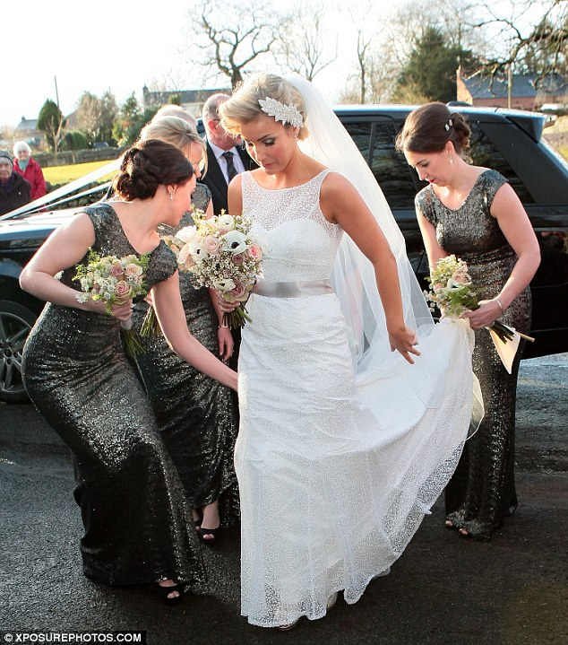 Helping hands: Helen's three bridesmaids helped to straighten out her dress as she prepared to make her way into the church
