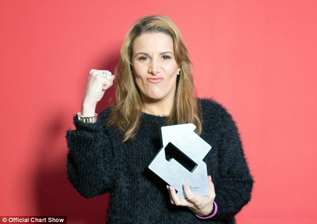 She did it! The X Factor winner made a fist after reaching the top spot with her debut single