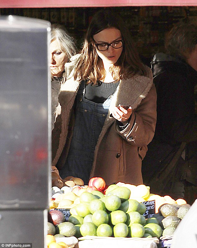 Getting her five-a-day: The pretty brunette checks her phone as she surveys some local produce