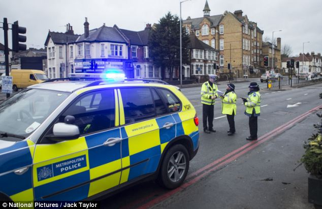 Police: Officers at the scene on Bowes Road, north London this morning. The Met is appealing for witnesses