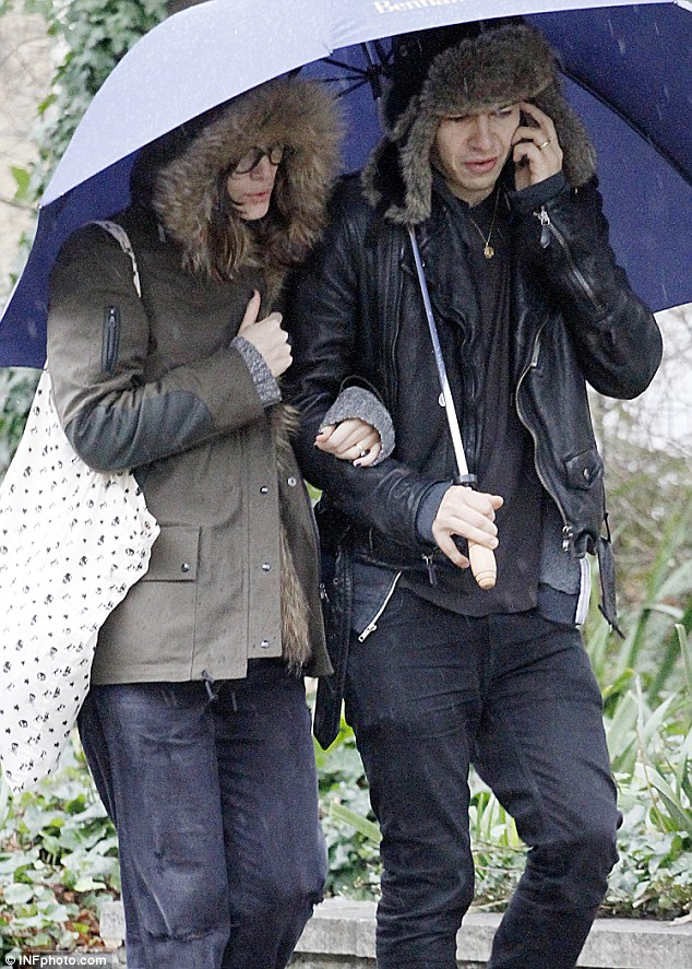 Cuddle up: Keira put her arm round her husband's as they hugged beneath the umbrella