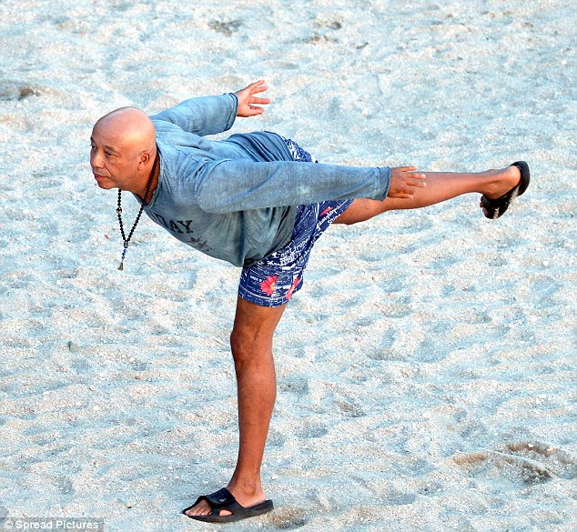 Warrior I pose: Russell was dressed very casually for the sandy outing in blue patterned swim trunks, a lived-in 'Sunday' long-sleeve shirt, and black slippers