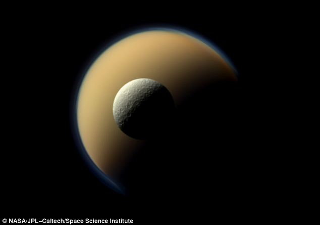 Saturn's largest and second largest moons, Titan and Rhea, appear to be stacked on top of each other in this true-color scene from the Cassini spacecraft