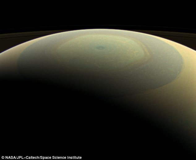 The globe of Saturn resembles a holiday ornament in a wide-angle image overlooking its north pole, bringing into view the hexagonal jet stream and rapidly spinning polar vortex that reside there