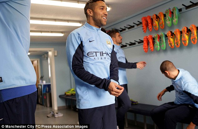 Christmas spirit: Gael Clichy smiles in the changing rooms at Carrington before heading out for City's last training session before Christmas