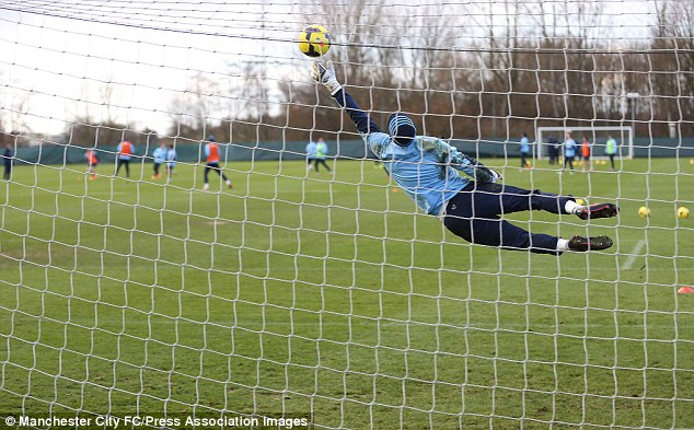 Joe Hart makes a save during shooting practice in Manchester City's training session on Christmas Eve