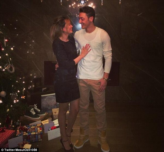 Festive spirit: Mesut Ozil poses with girlfriend Many Capristo, but we're not sure about the visible vest line...