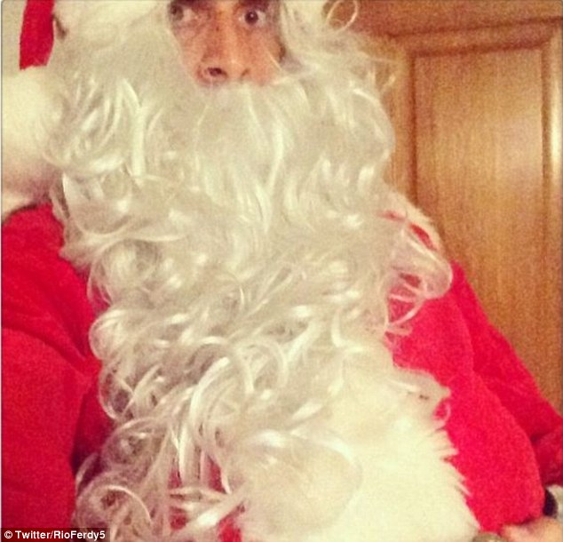 Guess who? Rio Ferdinand gets into the festive spirit by dressing as Santa Claus on Christmas Eve